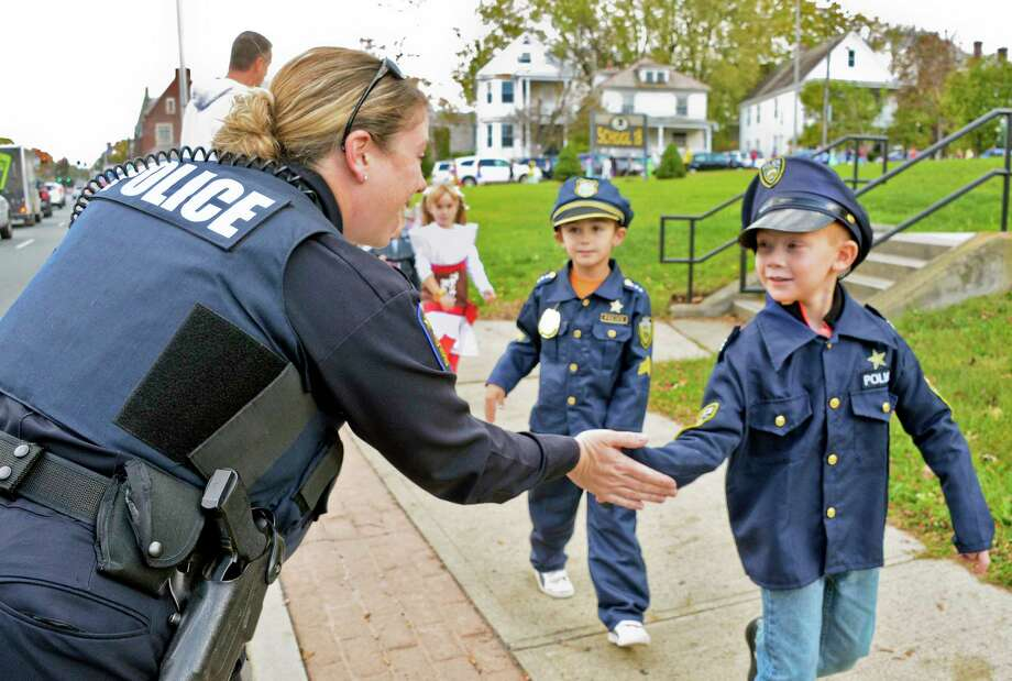 Police officer Karrie Hoover greets costumed policemen Jack Lord and Austin Kannif as they march in School 18's annual Halloween parade Tuesday Oct. 31, 2017 in Troy, NY. Photo: John Carl D'Annibale / 20041986A