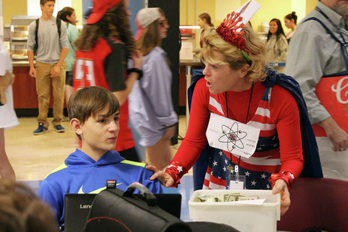 Wilton High School science teacher Patricia Rinaldi, dressed as Atomic Girl, went around the cafeteria on Halloween, Tuesday, collecting donations for those affected in Puerto Rico.