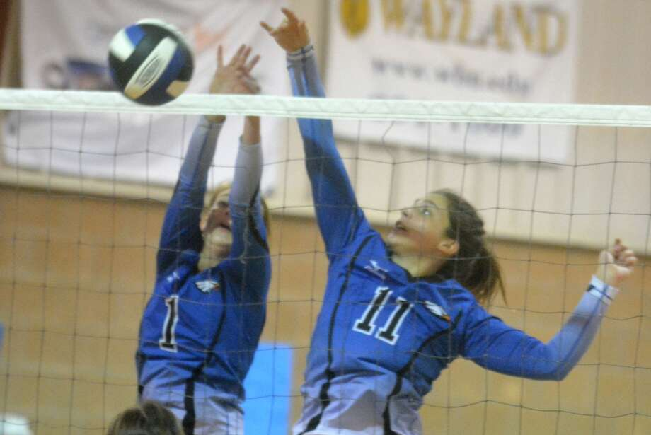 Plainview Christian Academy's Kylee Hill, 1, and Hanna Craig, 11, go above the net to thwart an opponent's scoring attempt during a volleyball match earlier this season. The Lady Eagles' season came to an end when they were edged in five games by Fort Worth Bethesda Christian in the TAPPS Class 2A area round of the playoffs. Photo: Skip Leon/Plainview Herald