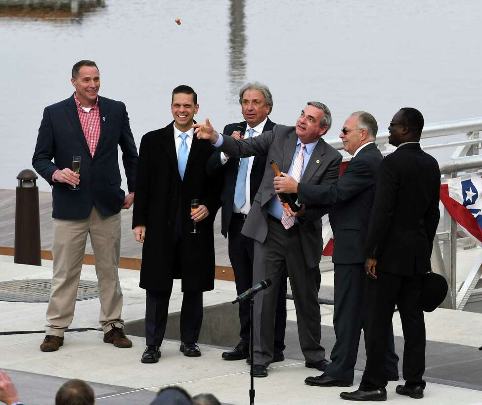 Assemblyman Angelo Santabarbara, second from left, David Buicko, president and CEO of the Galesi Group, and others, watch as Mayor Gary McCarthy, third from right, pops the cork on a bottle of bubbly during a ceremony to mark the completion of the marina at Mohawk Harbor on Wednesday, Nov. 1, 2017, in Schenectady, N.Y. The signature element of a $480 million mixed-use development is ready for public use and includes 50 boat slips, amphitheater, and kayak launch. (Will Waldron/Times Union)