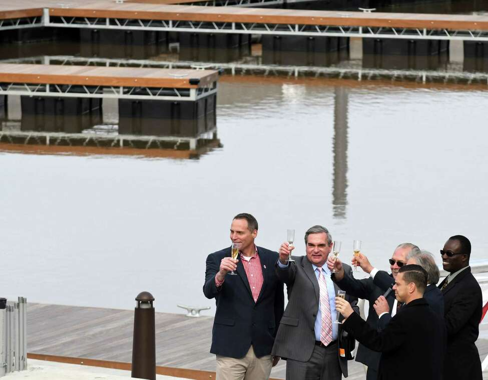 Mayor Gary McCarthy, second from left, raises a glass during a ceremony to mark the completion of the marina at Mohawk Harbor on Wednesday, Nov. 1, 2017, in Schenectady, N.Y. The signature element of a $480 million mixed-use development is ready for public use and includes 50 boat slips, amphitheater, and kayak launch. (Will Waldron/Times Union)