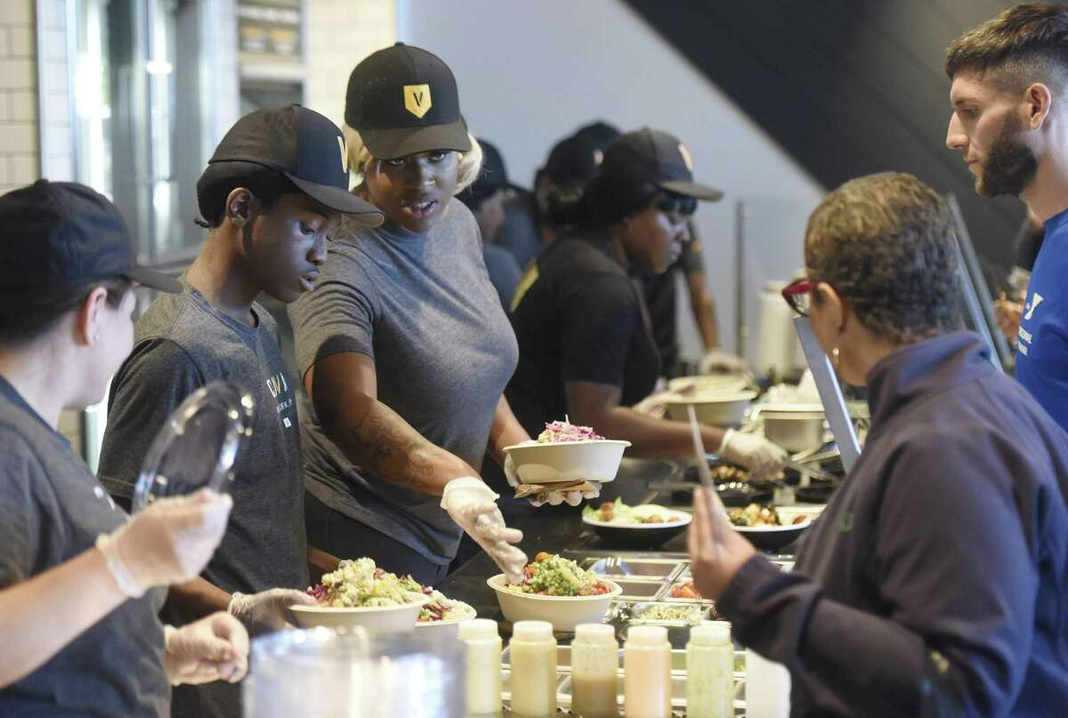 Folks order food from the casual Greek Mediterranean restaurant Cava during its free community lunch at the new location in Greenwich, Conn. Tuesday, Oct. 31, 2017. Restaurant-goers ate for free from noon to 2 p.m. Tuesday and the official grand opening of the restaurant is Wednesday.