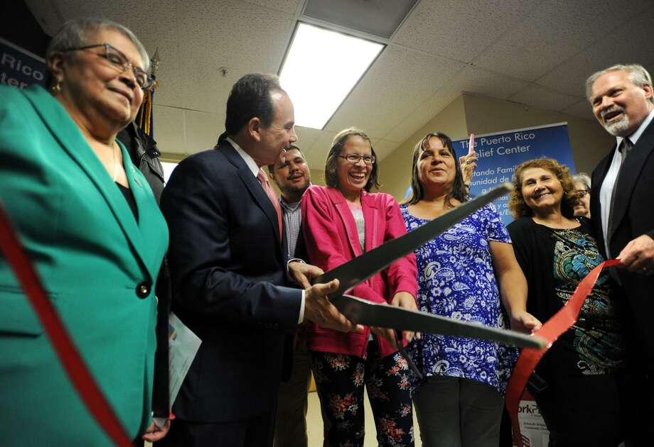 Erica Rosario Morales and her mother Fanny Morales Herrera, from Hatillo, Puerto Rico, cut the ribbon on the new Puerto Rico Relief Center at Career Resources, Inc. at 2 Lafayette Square in Bridgeport, Conn. on Wednesday, November 1, 2017. From left are center Coordinator Rosa Correa, Bridgeport Mayor Joe Ganim, State Rep. Chris Rosario, Rosario Morales, Morales Herrera, City Clerk Lydia Martinez, and Career Resources Executive Director Scott Wilderman. Photo: Brian A. Pounds / Hearst Connecticut Media / Connecticut Post