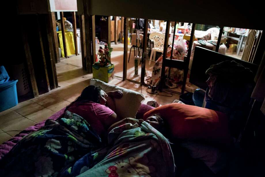 Rebecca Chavez, left, and her sister, Angelica Chavez, share an air mattress as they fall asleep Tuesday, Sept. 19, 2017 in Houston. The family is still sleeping in their home even though four feet of the walls have been removed after Hurricane Harvey. Photo: Michael Ciaglo, Houston Chronicle / Michael Ciaglo
