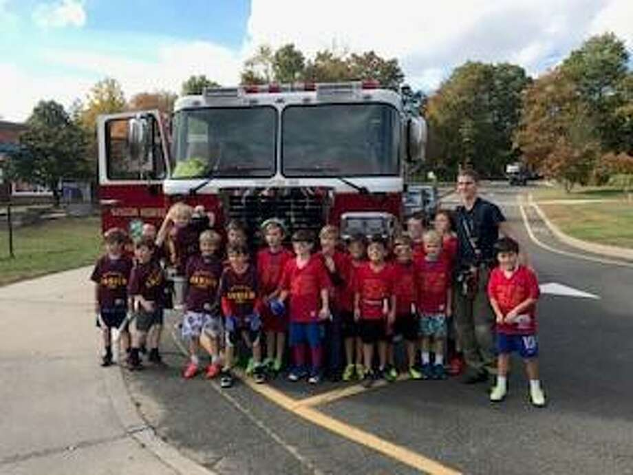 Both the Darien FD and Noroton Heights FD teams pose after their 'Heroes Bowl' game. Photo: Contributed Photo / Darien News contributed