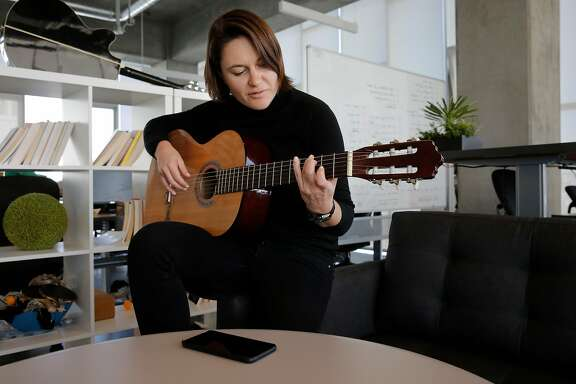 Eugenia Kuyda,CEO of Replika, takes a break to play guitar at their office in San Francisco, Ca. on Monday October 30, 2017. Replika a San Francisco start up that is offering people an unusual use of artificial intelligence, an app you train to know you, to mirror your voice, responses, speech patterns, likes and dislikes to become your digital confidant.