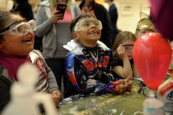 Zander and Bella Gomez participate in activities with volunteers from the Midland College chemistry club during a spooky science themed Family Science Night Oct. 31, 2017, at the Petroleum Museum. James Durbin/Reporter-Telegram