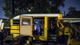 Manuel Perea sleeps in a converted school bus in the backyard of his flood-damaged rental home.