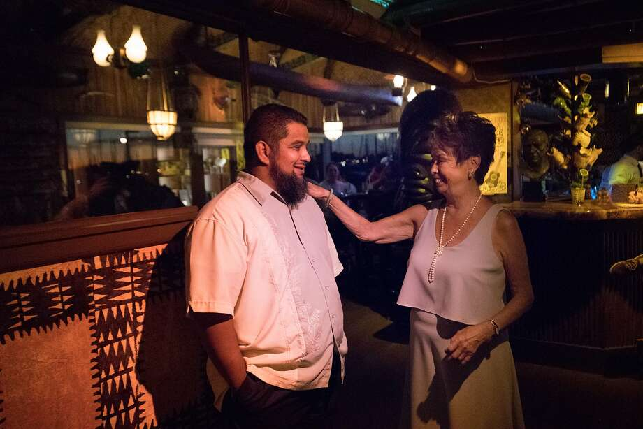Retiring Claudette Lum, a hostess for Trader Vic's since 1960, speaks with Willie Hernandez. Photo: Paul Kuroda, Special To The Chronicle