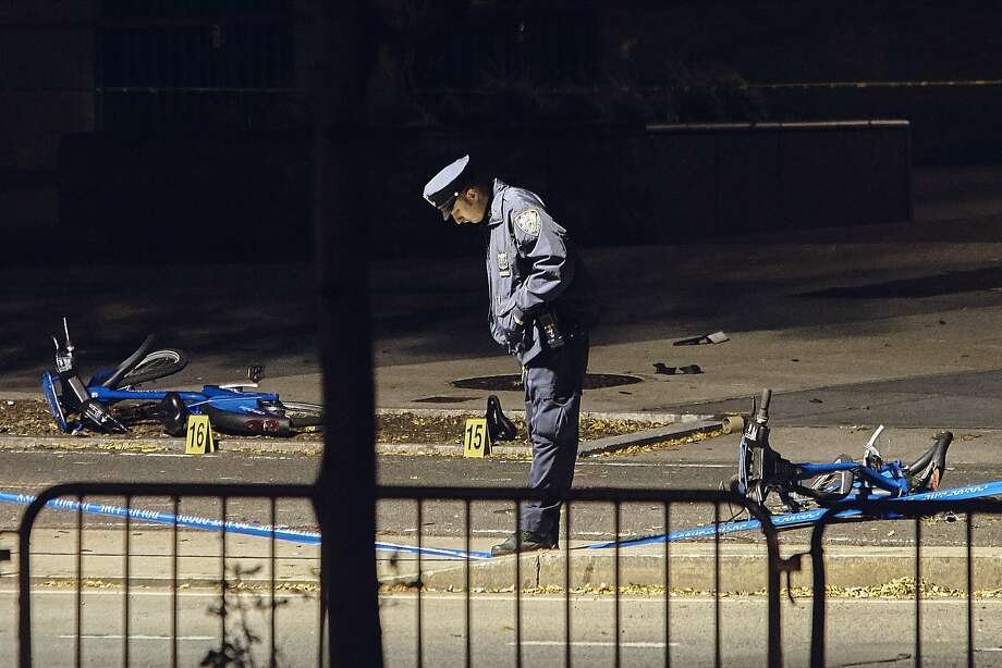 A police officer stands guard next to bicycles that lie on the bike path where a truck driver plowed into crowds of people. Photo: Andres Kudacki, Associated Press