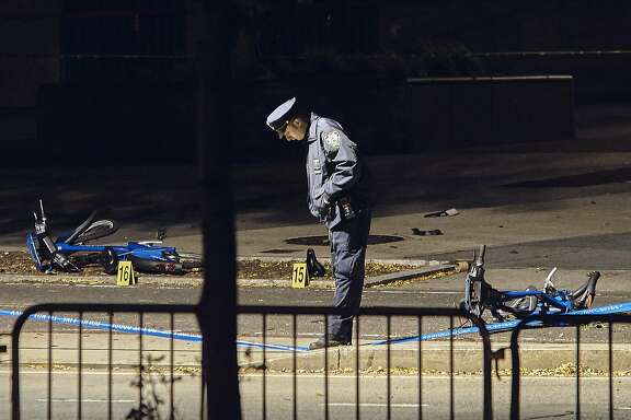 A police officer stands guard next to bicycles Wednesday, Nov. 1, 2017, that lie on a bike path at the crime scene after a motorist Tuesday drove onto the path near the World Trade Center memorial, striking and killing several people, in New York. (AP Photo/Andres Kudacki)