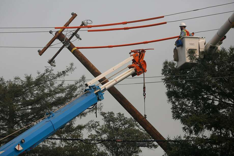 Workers from PG&E replace a downed power line on Cleveland Avenue in Santa Rosa. PG&E gave its first estimate Thursday of the costs of restoring service to the 360,000 customers who lost power during the Wine Country fires. Photo: Leah Millis, The Chronicle