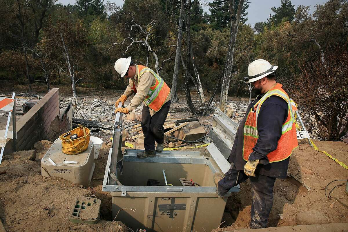 Gary Sheperson, PG&E cable splicer and Jared Rubio, PG&E apprentice cable splicer, work to restore a main power line along Deer Hollow Drive on Tuesday, October 17, 2017 in Napa.