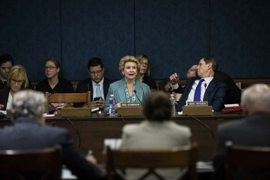 Sen. Debbie Stabenow, D-Michigan, speaks as Sen. Ron Wyden, D-Oregon,talks to an aide during a meeting about the GOP tax plan by the Democratic Policy and Communications Committee on Capitol Hill on Wednesday. House Republicans are expected to unveil their tax reform plan on Thursday. Photo: Getty Images / 2017 Getty Images