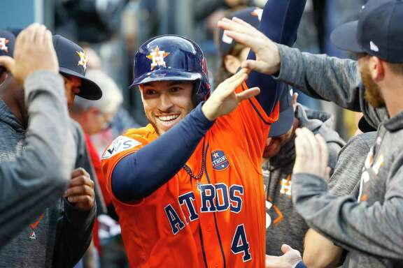 Houston Astros center fielder George Springer (4) celebrates in the dugout after being driven in by a Alex Bregman hit during the first inning of Game 7 of the World Series at Dodger Stadium on Wednesday, Nov. 1, 2017, in Los Angeles.
