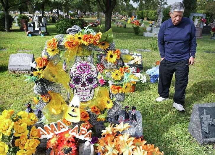 Robert Guerrero  walks away from his parents' and brother's grave after placing flowers for El Día de los Muertos.