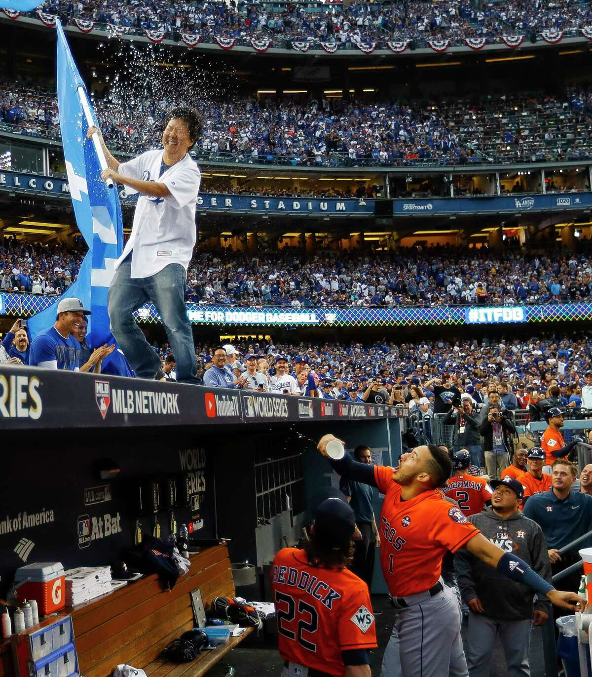 Houston Astros shortstop Carlos Correa (1) throws water at actor Ken Jeong on top of the Astros dugout with a Dodgers flag before Game 7 of the World Series at Dodger Stadium on Wednesday, Nov. 1, 2017, in Los Angeles.