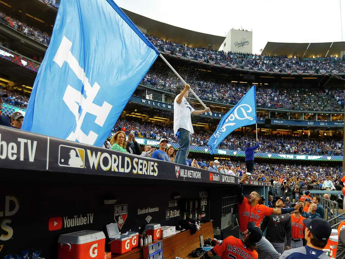 PHOTOS: More of the water toss and other festivities before Game 7 of the World Series Houston Astros shortstop Carlos Correa (1) throws water at actor Ken Jeong on top of the Astros dugout with a Dodgers flag before Game 7 of the World Series at Dodger Stadium on Wednesday, Nov. 1, 2017, in Los Angeles.