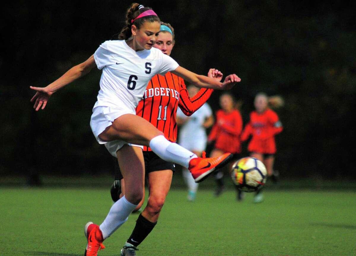 Staples' Mia Gonzalez kicks the ball downfield as Ridgefield's Caitlin Slaminko tries to intercept during Wednesday's FCIAC semifinal.