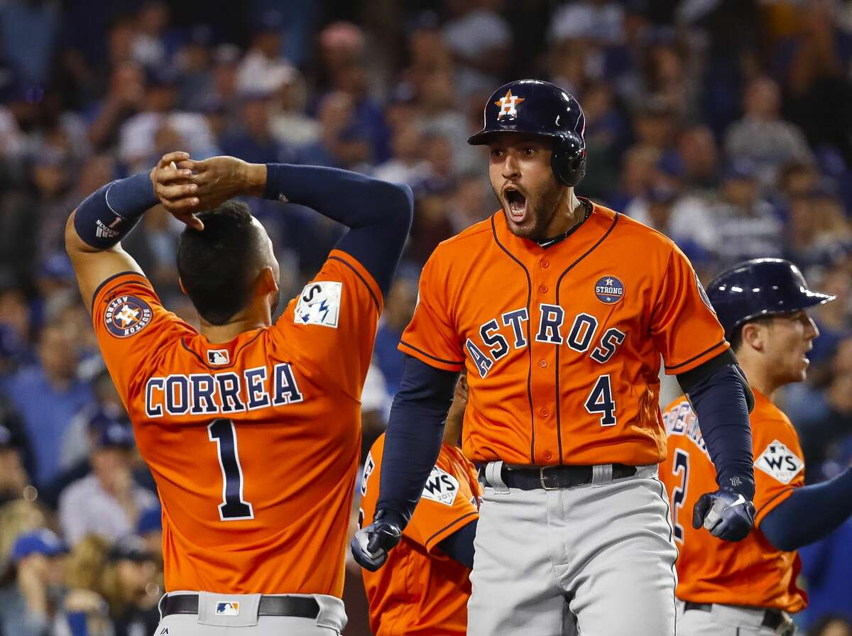 Houston Astros shortstop Carlos Correa (1) greets George Springer after Springer hit a two-run home run in the second inning of Game 7 of the World Series at Dodger Stadium on Wednesday, Nov. 1, 2017, in Los Angeles.