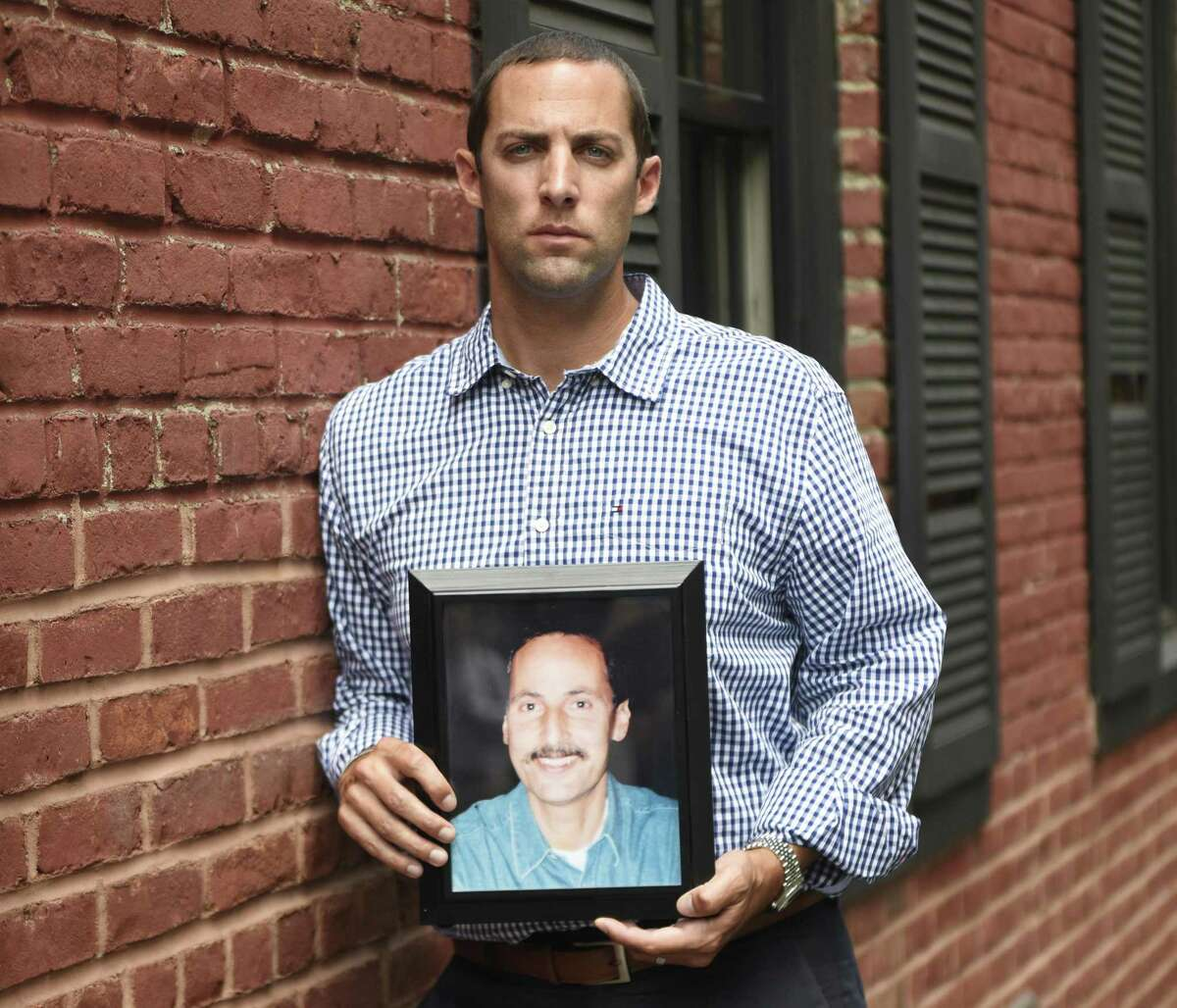 Michael Pascuma poses with a photograph of his father. As a was a 20-year-old student at Sacred Heart University, Pascuma lost his father, Michael, in the World Trade Center attacks 9/11.