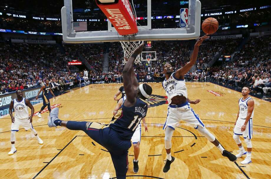 Warriors forward Kevin Durant (35) , swatting away a shot by Pelicans guard Jrue Holiday (11), Durant is second in the NBA with 2.4 blocks per game. Photo: Gerald Herbert / AP / Copyright 2017 The Associated Press. All rights reserved.