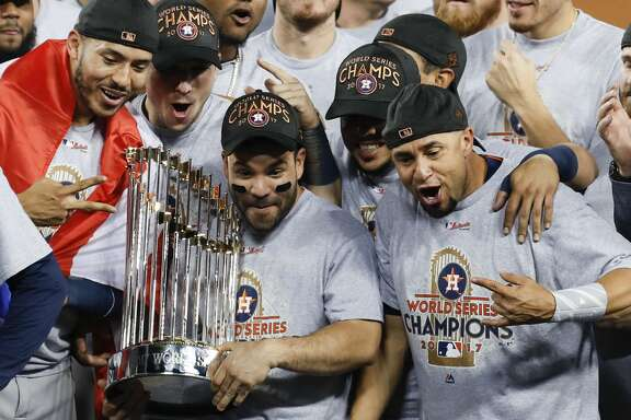 Houston Astros second baseman Jose Altuve (27) holds the  the World Series trophy as the Astros celebrate beating the Los Angeles Dodgers 5-1 in Game 7 of the World Series at Dodger Stadium on Wednesday, Nov. 1, 2017, in Los Angeles. The Astros took the Series 4-games-to-3 to capture the franchise's first title.