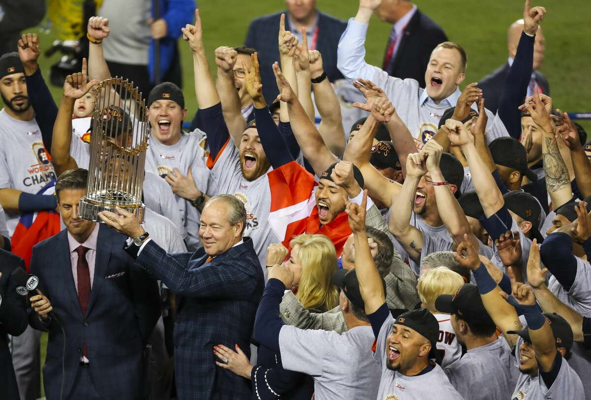 The Houston Astros celebrate as owner Jim Crane holds up the World Series trophy after Game 7 of the World Series at Dodger Stadium on Wednesday, Nov. 1, 2017, in Los Angeles.
