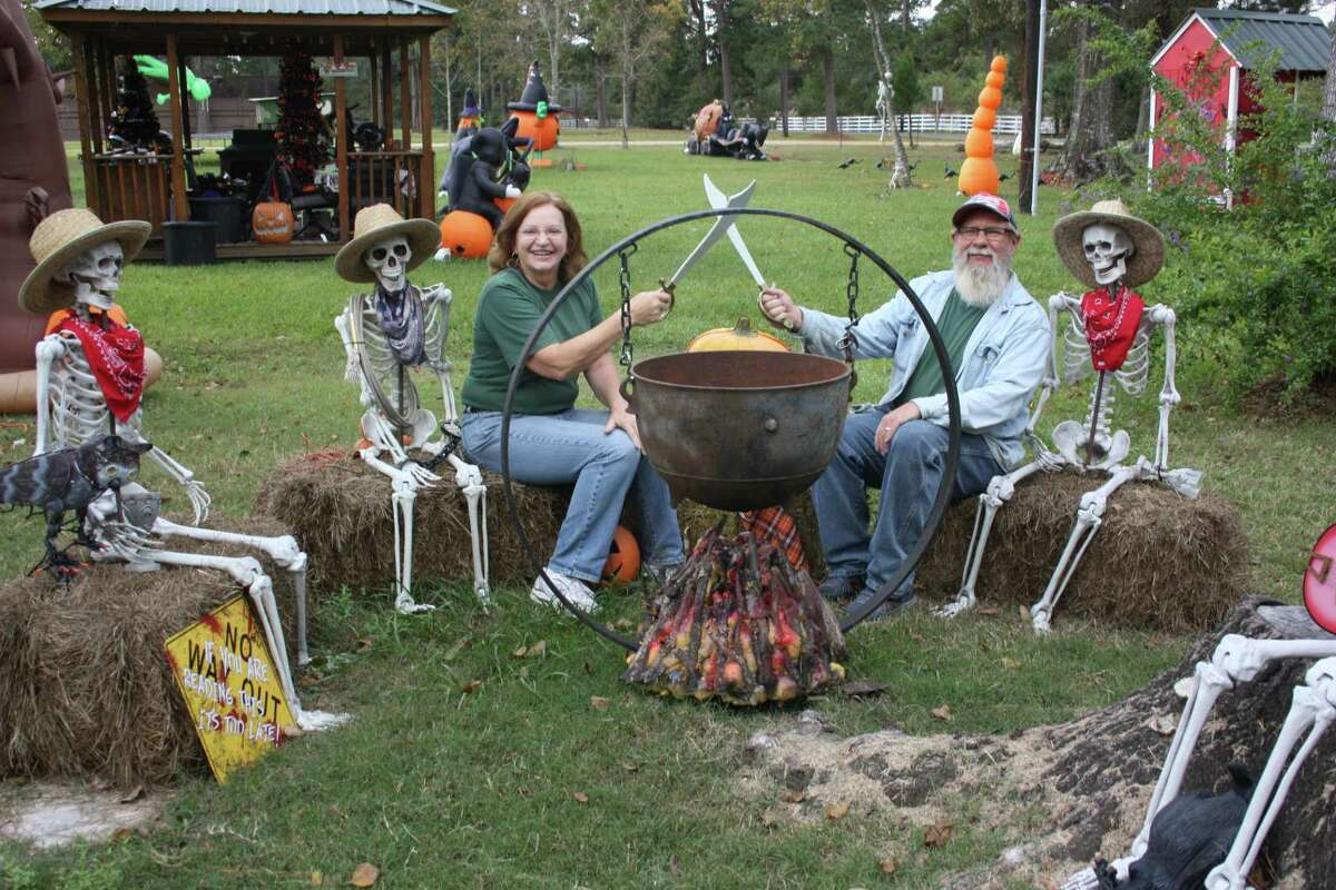 Bill and Pat Baker engage in a little sword play while sitting among their skeletal cowboys. The Bakers' front yard in Cleveland has dozens of Halloween decorations that will soon be moved to make way for Christmas.