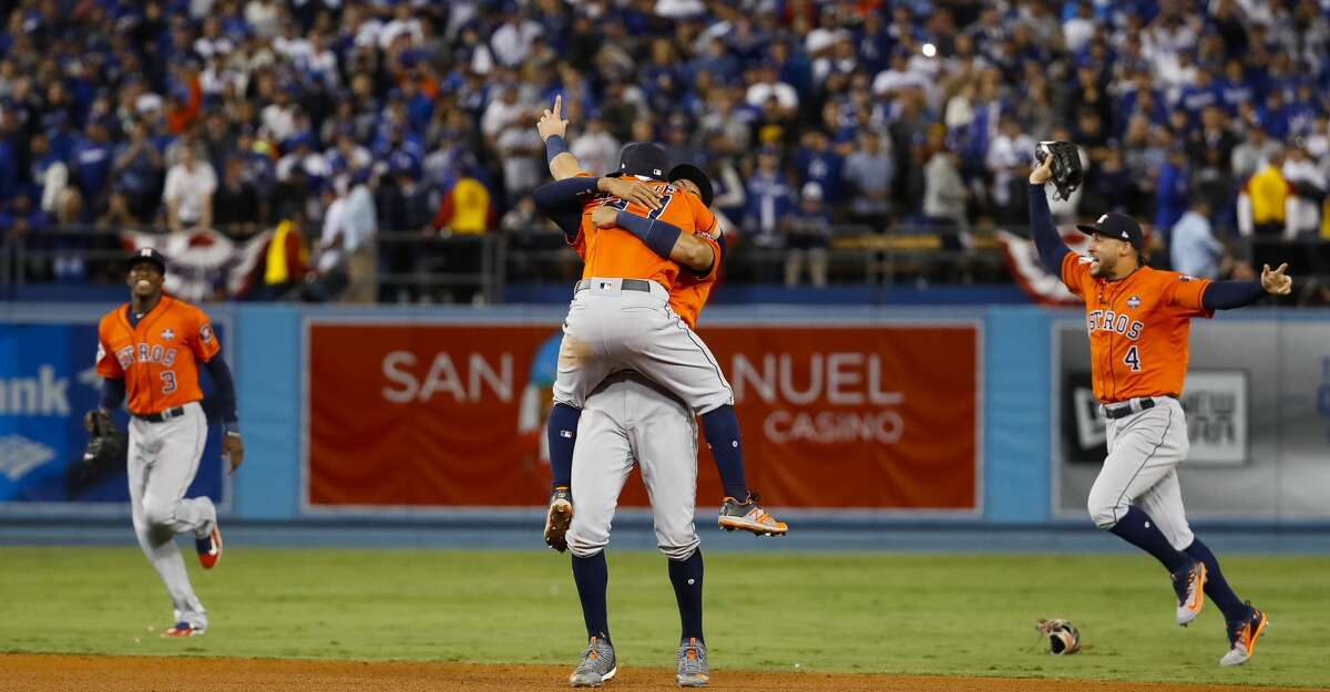 Houston Astros shortstop Carlos Correa (1) picks up second baseman Jose Altuve (27) as center fielder Cameron Maybin (3) and center fielder George Springer (4) celebrate the Astros 5-1 win in Game 7 of the World Series at Dodger Stadium on Wednesday, Nov. 1, 2017, in Los Angeles. ( Karen Warren / Houston Chronicle )