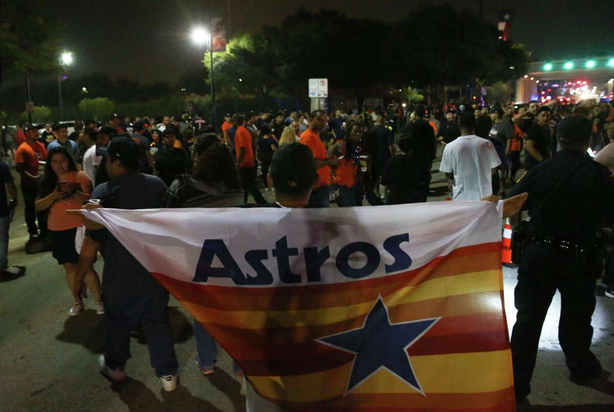 A Houston Astros fan wraps himself in a vintage Astros flag as he celebrates the Houston Astros' World Series Championship on Texas Avenue on Wednesday, Nov. 1, 2017, in Houston.