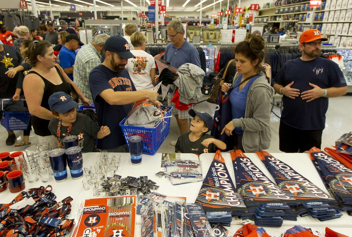 Felix Ramirex picks through championship gear with his wife Lorena and his two sons Felix III and Manny at Academy on North Loop 336 after the Houston Astros defeated the Los Angeles Dodgers 5-1 in Game 7 of the World Series, Wednesday, Nov. 1, 2017, in Conroe.