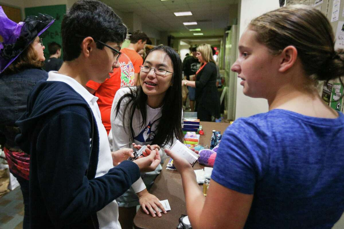 The John Cooper School freshmen Danielle Pham, center, and Dorothea Johnson, right, sort supplies for military care packages with classmates during the Cooper Cares Day on Tuesday, Oct. 31, 2017, at The John Cooper School.