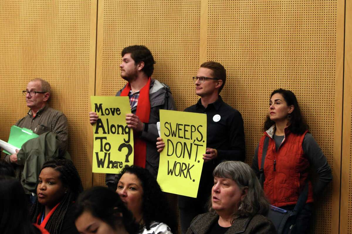 People hold signs inside a public hearing on the city budget, Wednesday, Nov. 1, 2017 at City Hall. Hundreds of housing activists turned up on the second anniversary of the City declaring the homelessness crisis a Civil State of Emergency, to protest the homeless camp sweeps and call for solutions to the crisis. Activists set up tents and camped overnight on the City Hall plaza and in the Bertha Knight Landis room.