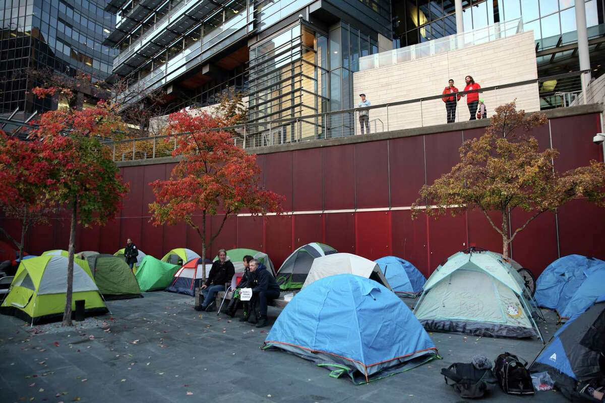People set up tents to occupy the City Hall plaza, as others attend a public hearing on the city budget, Wednesday, Nov. 1, 2017 at City Hall. Hundreds of housing activists turned up on the second anniversary of the City declaring the homelessness crisis a Civil State of Emergency, to protest the homeless camp sweeps and call for solutions to the crisis. Activists set up tents and camped overnight on the City Hall plaza and in the Bertha Knight Landis room.