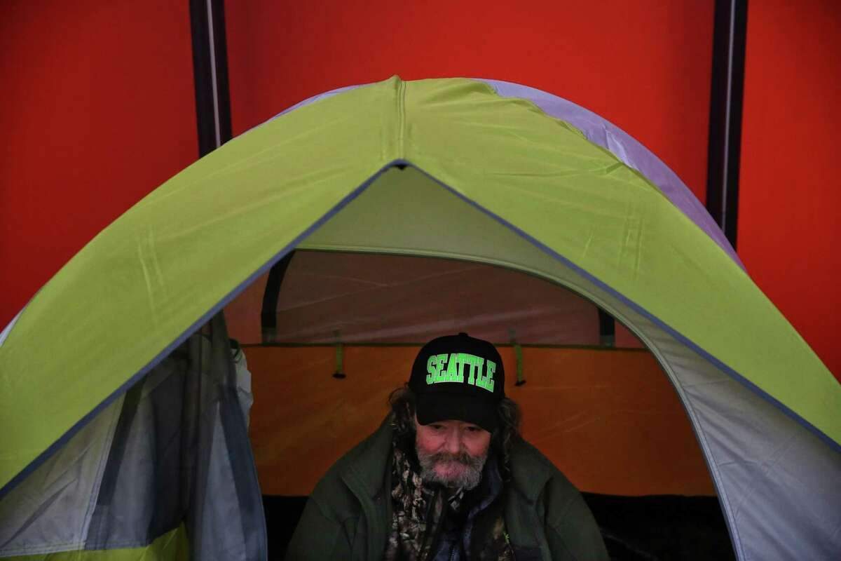 The annual count of people experiencing homelessness in Seattle and King County topped 12,000 in 2018, with a surge of people living in vehicles. Pictured: Robin Wes Hughes sits in his tent set up among others to occupy the City Hall plaza, as people attend a public hearing on the city budget, Wednesday, Nov. 1, 2017 at City Hall. Hundreds of housing activists turned up on the second anniversary of the City declaring the homelessness crisis a Civil State of Emergency, to protest the homeless camp sweeps and call for solutions to the crisis. Activists set up tents and camped overnight on the City Hall plaza and in the Bertha Knight Landis room.