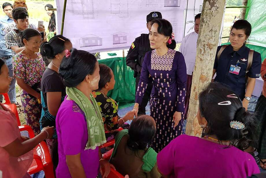 Aung San Suu Kyi (center) meets with residents in Rakhine State. An army campaign has forced most of the area's Rohingya Muslim population to flee to neighboring Bangladesh. Photo: STR, AFP/Getty Images