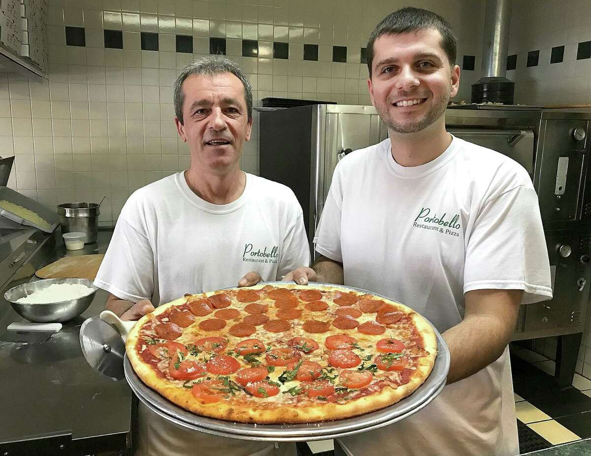 Kenny and Ilir Alka hold a half pepperoni, half tomato pizza at their restaurant, Portobello, in Brookfield, Conn., on Thursday, Nov. 2, 2017. Portobello is celebrating 20 years in business on Friday.