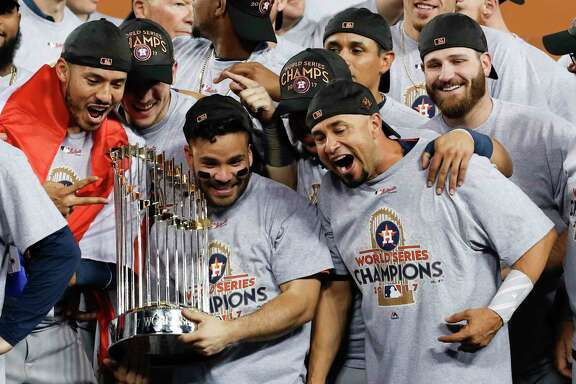 Houston Astros second baseman Jose Altuve (27) holds the  the World Series trophy as the Astros celebrate beating the Los Angeles Dodgers 5-1 in Game 7 of the World Series at Dodger Stadium on Wednesday, Nov. 1, 2017, in Los Angeles. The Astros took the Series 4-games-to-3 to capture the franchise's first title. ( Brett Coomer / Houston Chronicle )