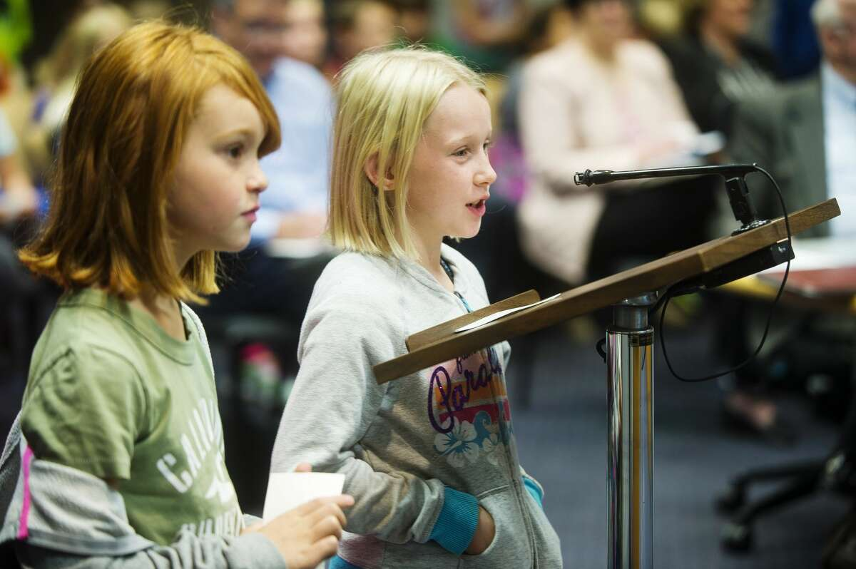 Meridian 4th graders Haylee Yorks, left, and Makayla Stockton present their suggested improvements for Sanford Lake Park to the Midland County Board of Commissioners on Oct. 17, 2017 in the County Services Building. (Katy Kildee/kkildee@mdn.net)