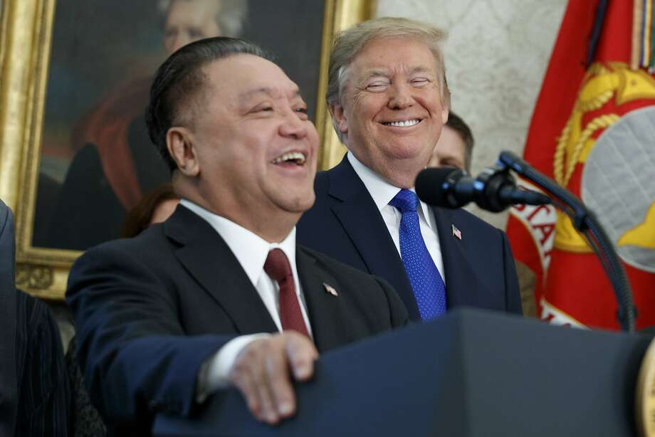 President Donald Trump smiles at Broadcom CEO Hock Tan during an event to announce that the company is moving its global headquarters to the United States, in the Oval Office of the White House, Thursday, Nov. 2, 2017, in Washington. The White House says Broadcom, a $100 billion semiconductor company based in Singapore, will move its home address to the U.S.  (AP Photo/Evan Vucci) Photo: Evan Vucci, Associated Press