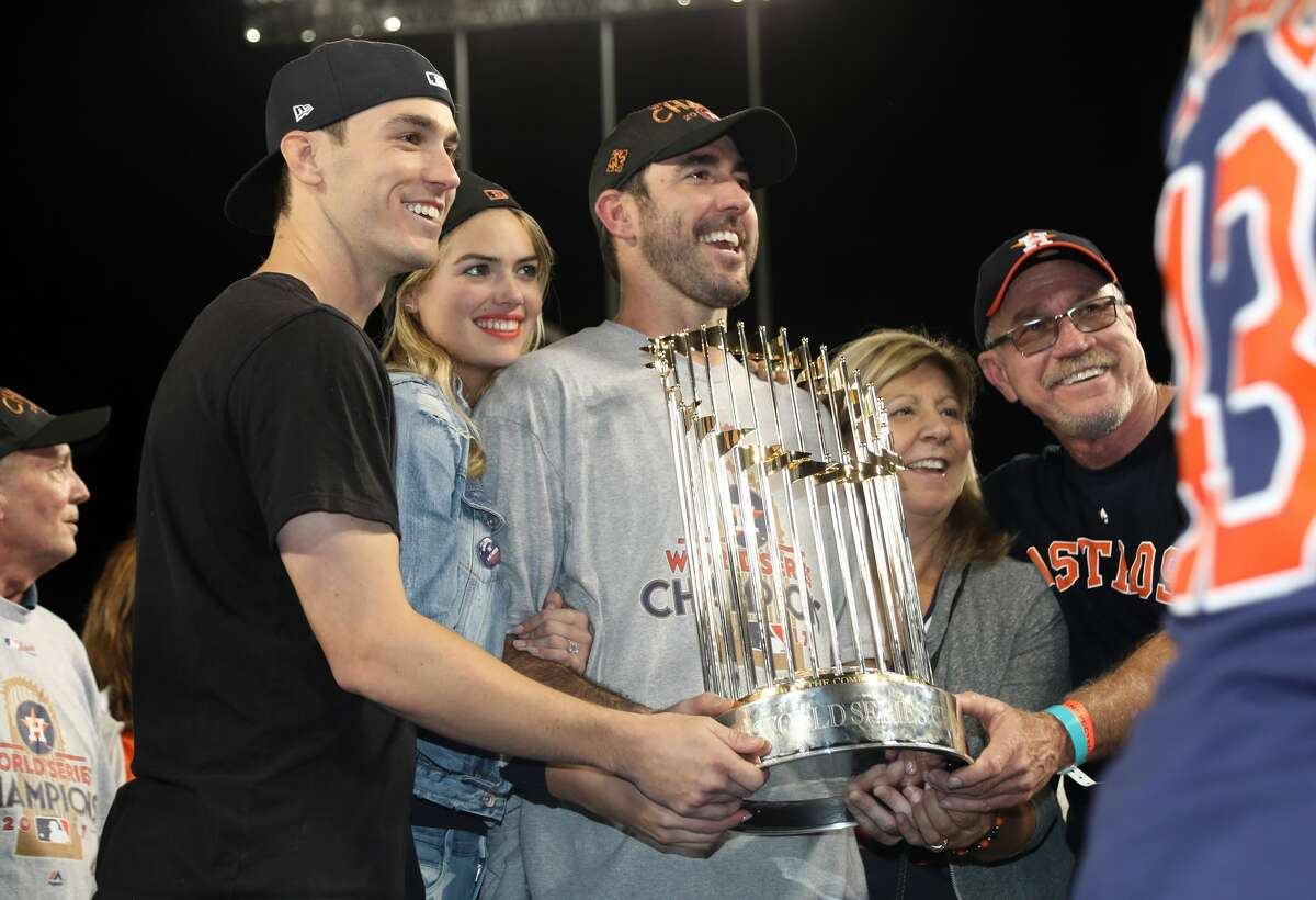 Kate Upton poses for a photo with boyrfriend Justin Verlander of the Houston Astros holding the The Commissioner's Trophy after the conclusion of The 2017 World Series - Game 7 at Dodger Stadium on November 1, 2017 in Los Angeles, California.