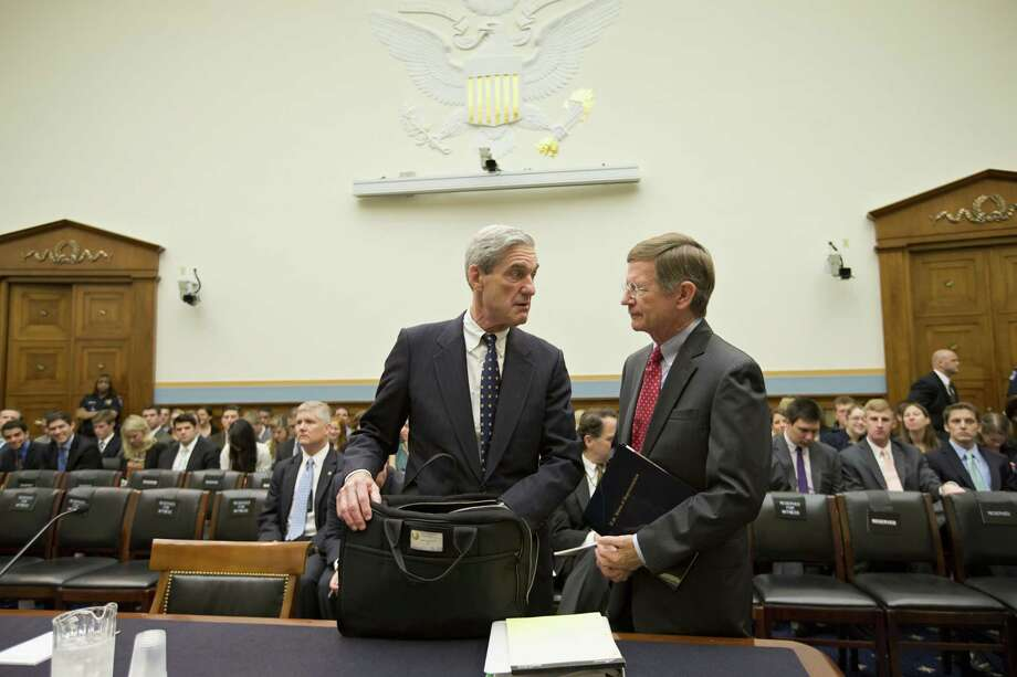 FBI Director Robert Mueller, left, talks with House Judiciary Committee member Rep. Lamar Smith, R-Texas, on Capitol Hill in Washington, Thursday, June 13, 2013, prior to the committee's oversight hearing on the FBI. Mueller is nearing the end of his 12 years as head of the law enforcement agency that is conducting high-profile investigations of the Boston Marathon bombings, the attacks in Benghazi, Libya, and leaks of classified government information. The committee's chairman, Rep. Bob Goodlatte, R-Va., said when it comes to national security leaks, it's important to balance the need to protect secrecy with the need to let the news media do their job. (AP Photo/J. Scott Applewhite) Photo: J. Scott Applewhite, STF / ASSOCIATED PRESS / AP2013