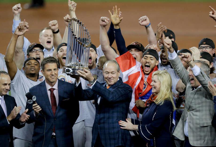 El propietario de los Astros de Houston, Jim Crane, levanta el trofeo de campeón de las Grandes Ligas rodeado por los jugadores y otros directivos de la franquicia en el Dodger Stadium de Los Ángeles, California. (AP / Alex Gallardo)