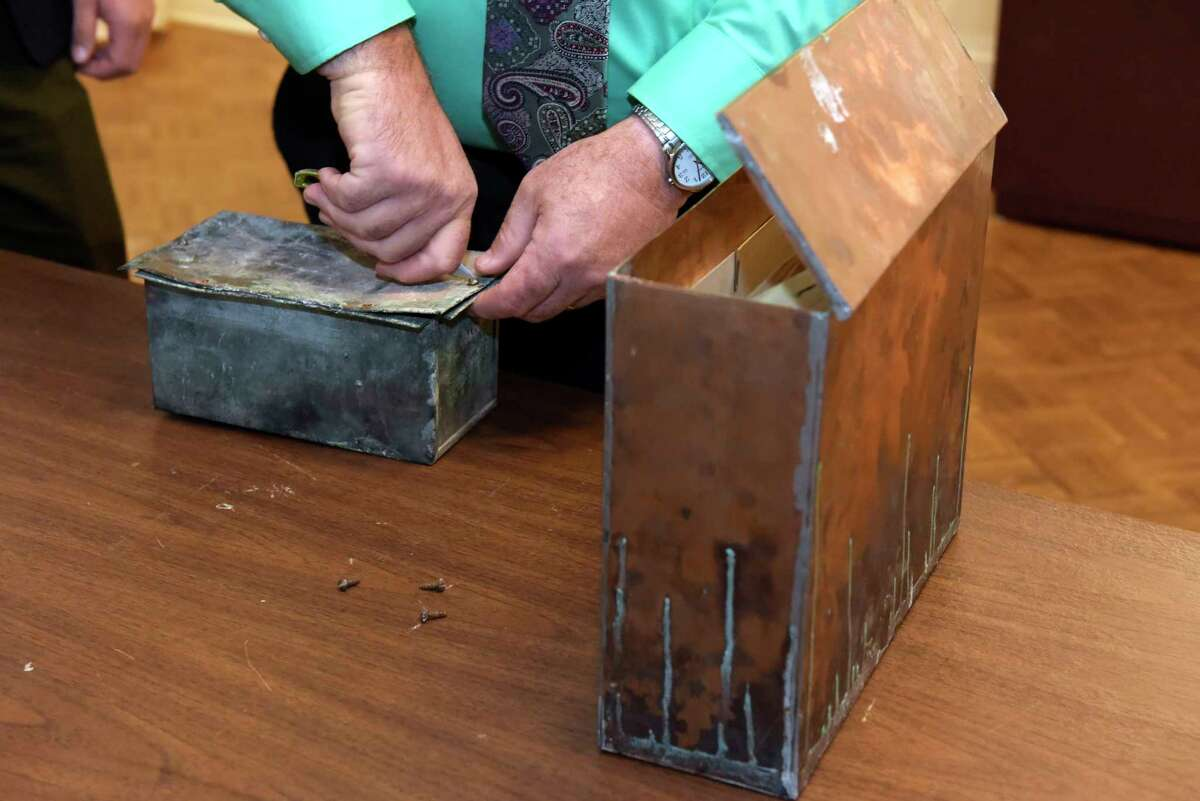 Tim Haskins, project manager with United Group of Companies, removes screws from a copper time capsule box at the Rensselaer County Historical Society on Thursday, Nov. 2, 2017, in Troy, N.Y. The time capsule was in a stone in a building that was the former Immaculate Conception seminary. On the right is another time capsule, from 1960 found inside another stone in the building complex. The College Suites at Hudson Valley were built on the site. (Paul Buckowski / Times Union)