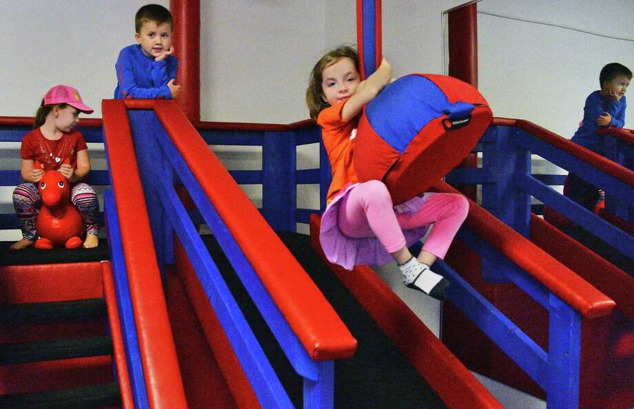 Four-year-old Molly Cook, left, of Ballston Spa, and Brendan Riggi, 6, of Saratoga Springs wait their turns as Emilia Millard, 5, of Saratoga Springs, right, rides a zip line before their yoga class at We Rock the Spectrum kid's gym Wednesday Oct. 25, 2017 in Ballston Spa, NY.  (John Carl D'Annibale / Times Union) Photo: John Carl D'Annibale / 20041889A