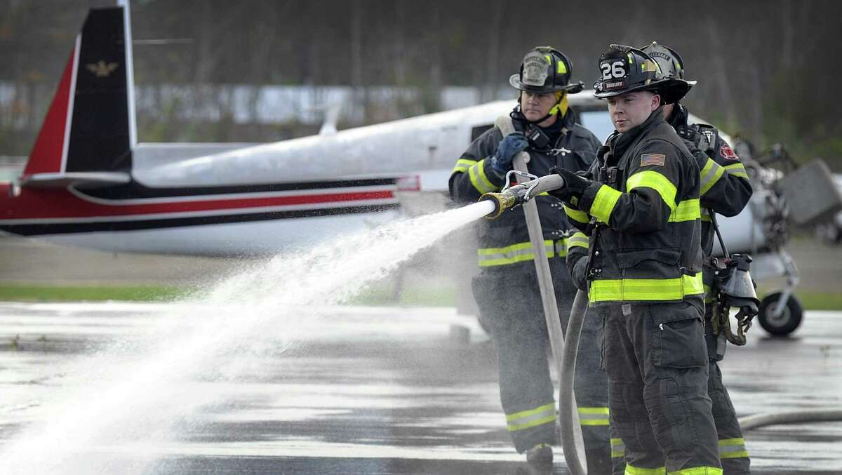 Danbury Firefighters use water and foam to contain a fire and oil spill resulting from a simulated plane crash at Danbury Airport Thursday, Nov.2, 2017. Emergency responders participated in an all-day emergency drill at the airport Thursday.