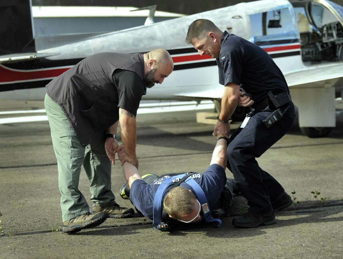 """Danbury Police Sgt. Mike Georgoulis, left, and Sgt. Marc Scocozza """"arest"""" Tyler Bergemann, Danbury deputy fire marshall who is """"a combative pilot"""" during an emergency training drill at Danbury Airport Thursday, Nov. 2, 2017."""