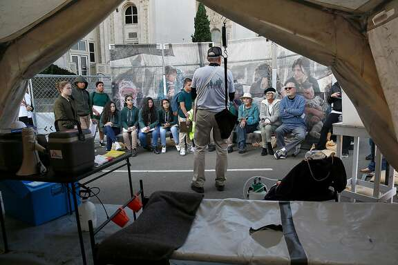 """Tour guide Jim Peck (middle) gives students from Lighthouse Community Charter School and visitors a view of a tent Doctors Without Borders would use to treat refugee patients at """"Forced From Home,"""" an interactive outdoor exhibition about the global refugee crisis at the Henry J Kaiser Convention Center parking lot on Tuesday, October 31, 2017, in Oakland, Calif."""