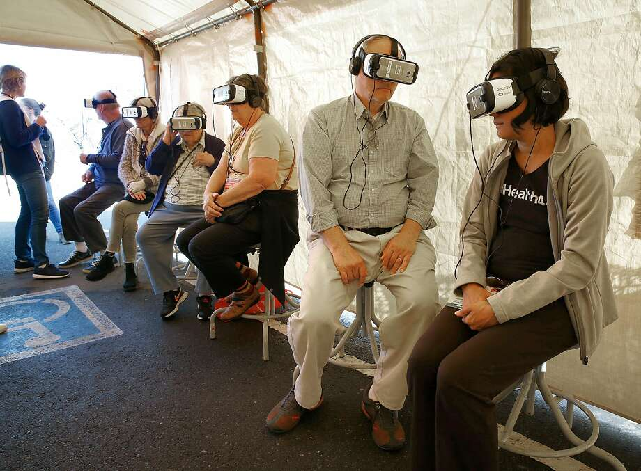 "Gary King  (second from right) from Minnesota joins his daughter Gala King (right) from Oakland as they look at different refugee camps  around the world through virtual reality at ""Forced From Home"" at the Henry J Kaiser Convention Center parking lot on Tuesday, October 31, 2017, in Oakland, Calif.. Photo: Liz Hafalia, The Chronicle"